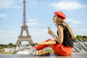 Young woman in red cap having a picnic with glass of wine and baguette sitting in front of the Eiffel tower in Paris ...