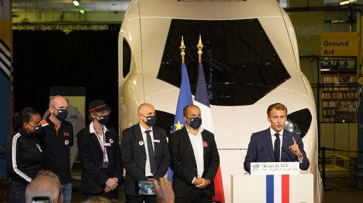 French President Emmanuel Macron (R) speaks at the TGV's unveiling.