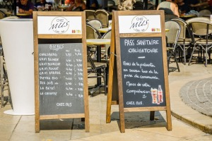 """A """"health pass required"""" sign at the entrance of a terrace restaurant in Aix en Provence, France."""
