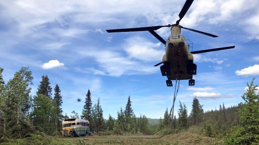 Alaska Army National Guard soldiers use a CH-47 Chinook helicopter to remove the abandoned bus.