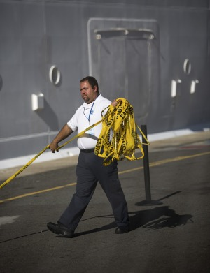 A West Indian Company employee removes a yellow caution barricade tape from around the Royal Caribbean International's ...