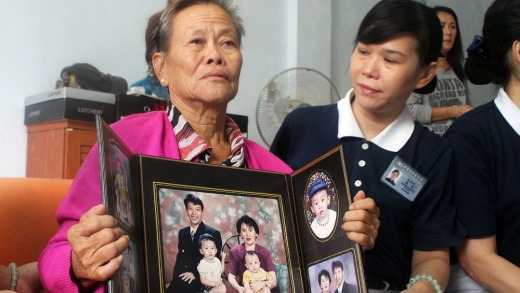 Grieving Indonesian mother Suharni displays a portrait of her son Sugianto Lo and wife Vinny Chynthya who are both ...