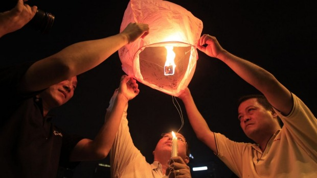 People prepare to release a sky lantern during a candlelight vigil for passengers aboard a missing Malaysia Airlines ...