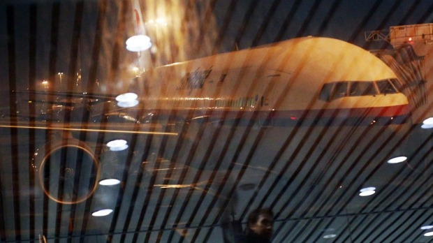 Malaysia Airlines Boeing flight MH318 to Beijing sits on the tarmac as passengers are reflected on the glass at the ...