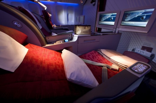 A Qatar Airways business class seat in recline position.