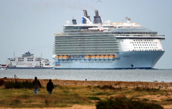 The world's largest cruise ship, Oasis of the Seas, dwarfs the Isle of Wight ferry as she enters The Solent, near ...