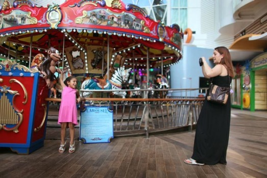Sarah Behle takes a photograph of her daughter, Hayden Behle, 5, in front of the carousel on board the cruise ship Oasis ...