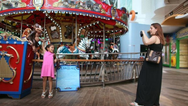 Sarah Behle takes a photograph of her daughter, Hayden Behle, 5, in front of the carousel on board the cruise ship Oasis of the Seas.