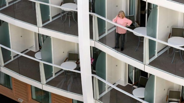 A person takes in the sights from the balcony of a stateroom on board the cruise ship Oasis of the Seas.