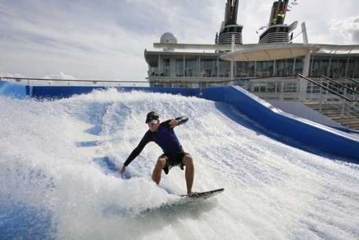 Royal Caribbean sports staff member Colin Kerr tries out one of two surf simulators on board the world's largest cruise ...