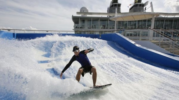 Royal Caribbean sports staff member Colin Kerr tries out one of two surf simulators on board the world's largest cruise ship, the Oasis of the Seas.