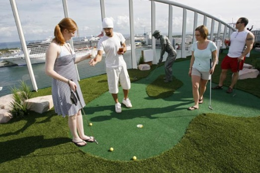 Passengers practise their putting on the world's largest cruise ship, the Oasis of the Seas. 15 decks on the ship house ...