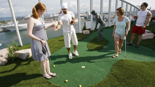 Passengers practise their putting on the world's largest cruise ship, the Oasis of the Seas. 15 decks on the ship house four main swimming pools, a park promenade, surf simulators, rock climbing, and miniature golf.