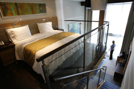 A two story crown loft suite with floor-to-ceiling windows and balcony on board the world's largest cruise ship, the ...