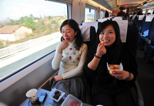 Passengers eat as they sit in a compartment of the train while it undergoes a test at the new railway station in Wuhan.
