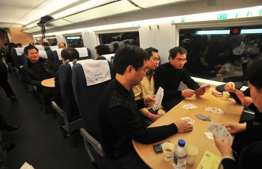 Passengers play cards as they sit in a compartment of a bullet train undergoing a test at the new railway station in Wuhan.