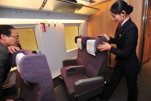 A stewardess moves a chair in a compartment of a bullet train undergoing a test at the new railway station in Wuhan.