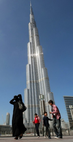 An Emirati woman and her children walk past Burj Dubai, the world's tallest tower.