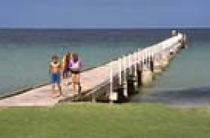 Kids walking off the jetty after swimming at Tumby Bay