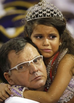 Controversial drum queen Julia Lira, 7, of the Viradouro samba school cries as she is carried by her father, Viradouro's ...