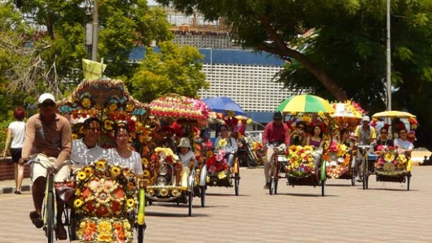 Colonial pace ... brightly decorated trishaws ferry tourists through the streets of Melaka.