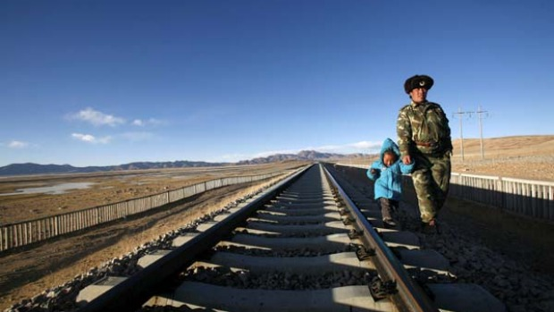 Top of the world ... a man walks along the Qinghai-Tibet railway track with his daughter.