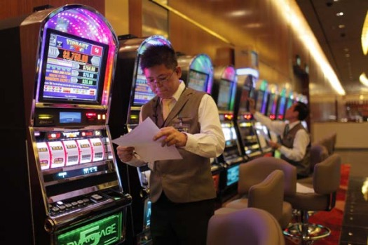 A dealer performs last minute checks on slot machines at the casino of the Marina Bay Sands.