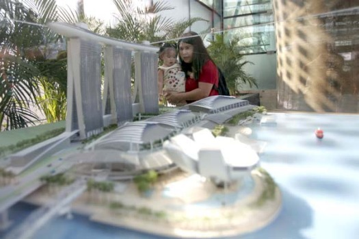 Visitors look at a miniature model of the Marina Bay Sands.
