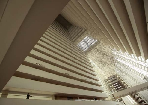 A man stands on a balcony inside the main lobby of the Marina Bay Sands resort hotel during its inauguration.