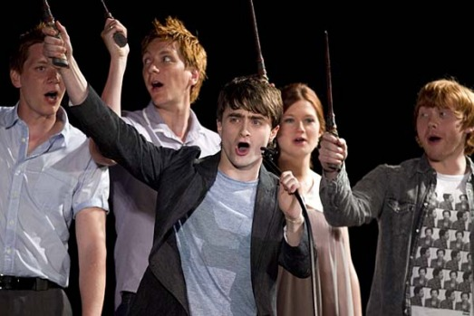 Daniel Radcliffe and members of the cast of Harry Potter wave their wands during the grand opening celebration for The ...