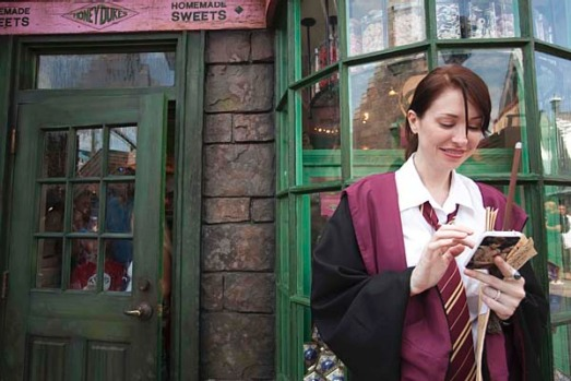 A guest, in her Hogwarts school regalia, uses a mobile phone during the grand opening for The Wizarding World of Harry ...