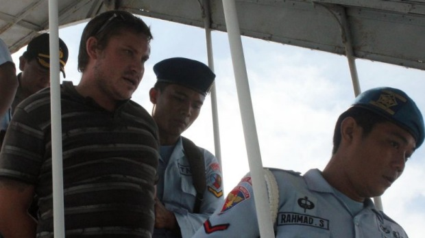 Australian Matt Christopher Lockley being taken off the flight by Indonesian officers.