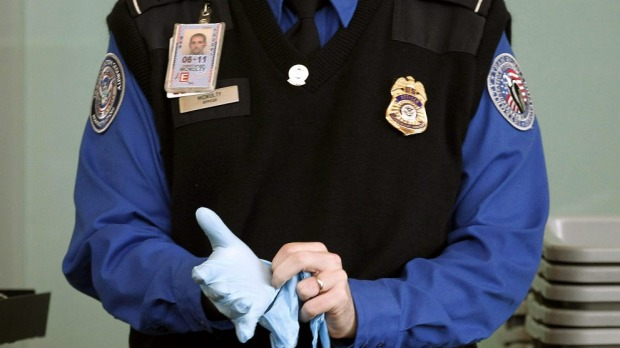 Charge your device prior travel or have it confiscated ... A Transportation Security Administration agent dons rubber ...