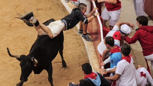 A runner tries to protect himself, at the San Fermin festival, in Pamplona.